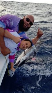 Hilly Awad and his daughter Amira Awad with the baby whale they had rescued.