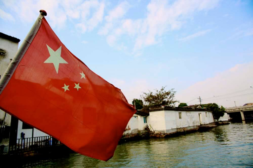 Chinese Flag at the back of a canal boat ride through water villages in Suzhou.