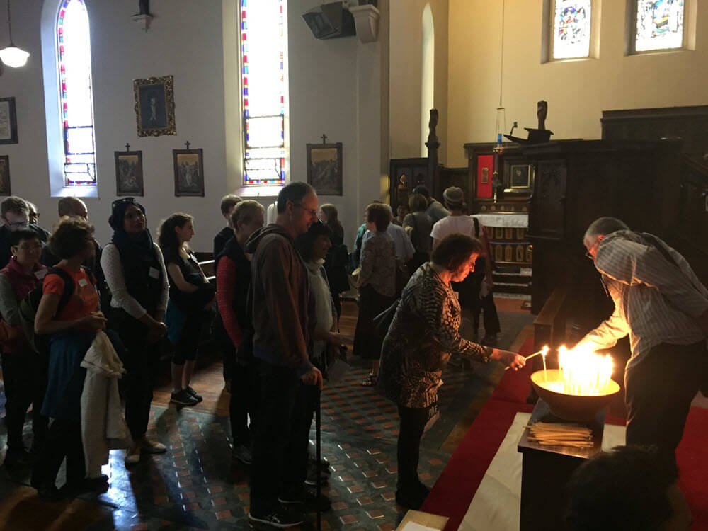 A woman lights a candle for peace at St Peters Church, Melbourne