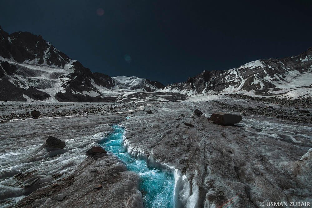 Water stream flowing over thick ice.